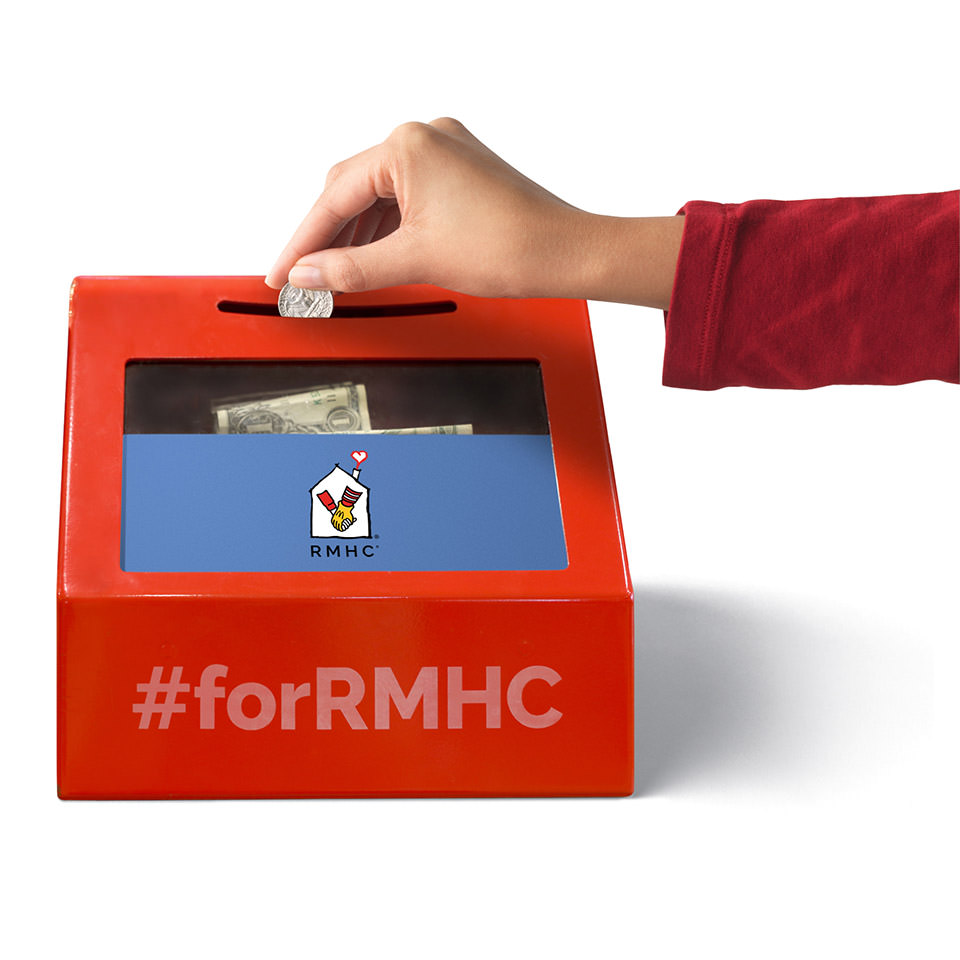 Hand putting coin in RMHC donation box