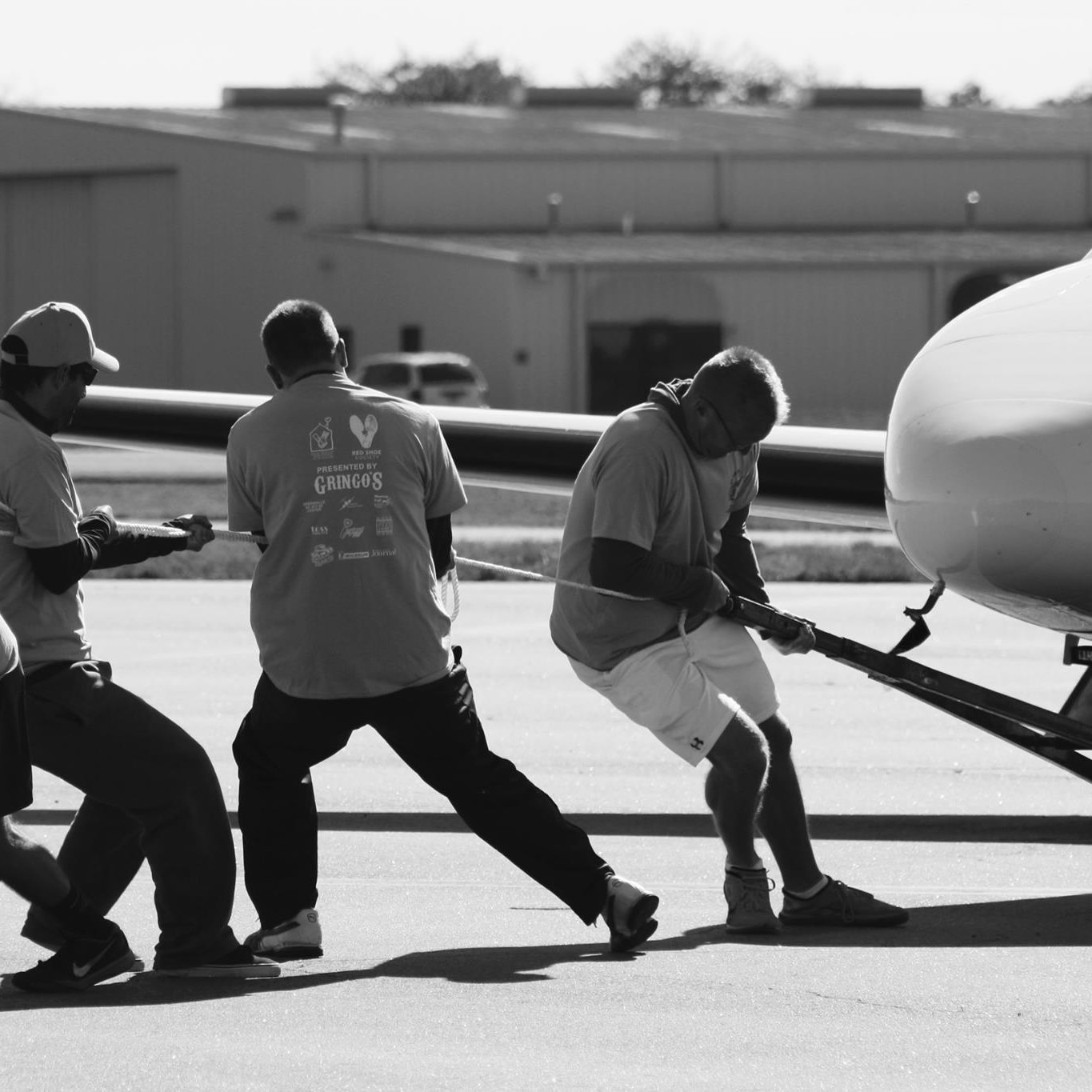 Three men pulling plane at plane pull event