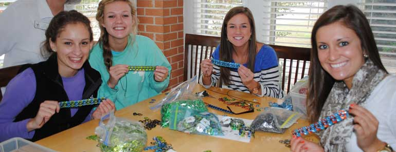 Four girls making pop tab bracelets
