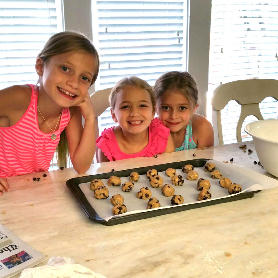 three young girls baking cookies