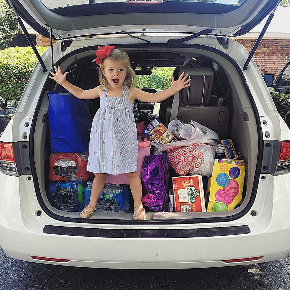 young girl standing in back of car with supplies