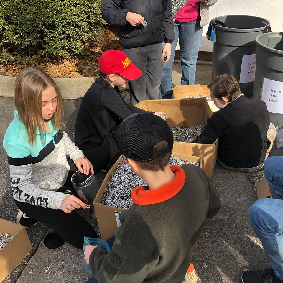 Children organizing pop tabs
