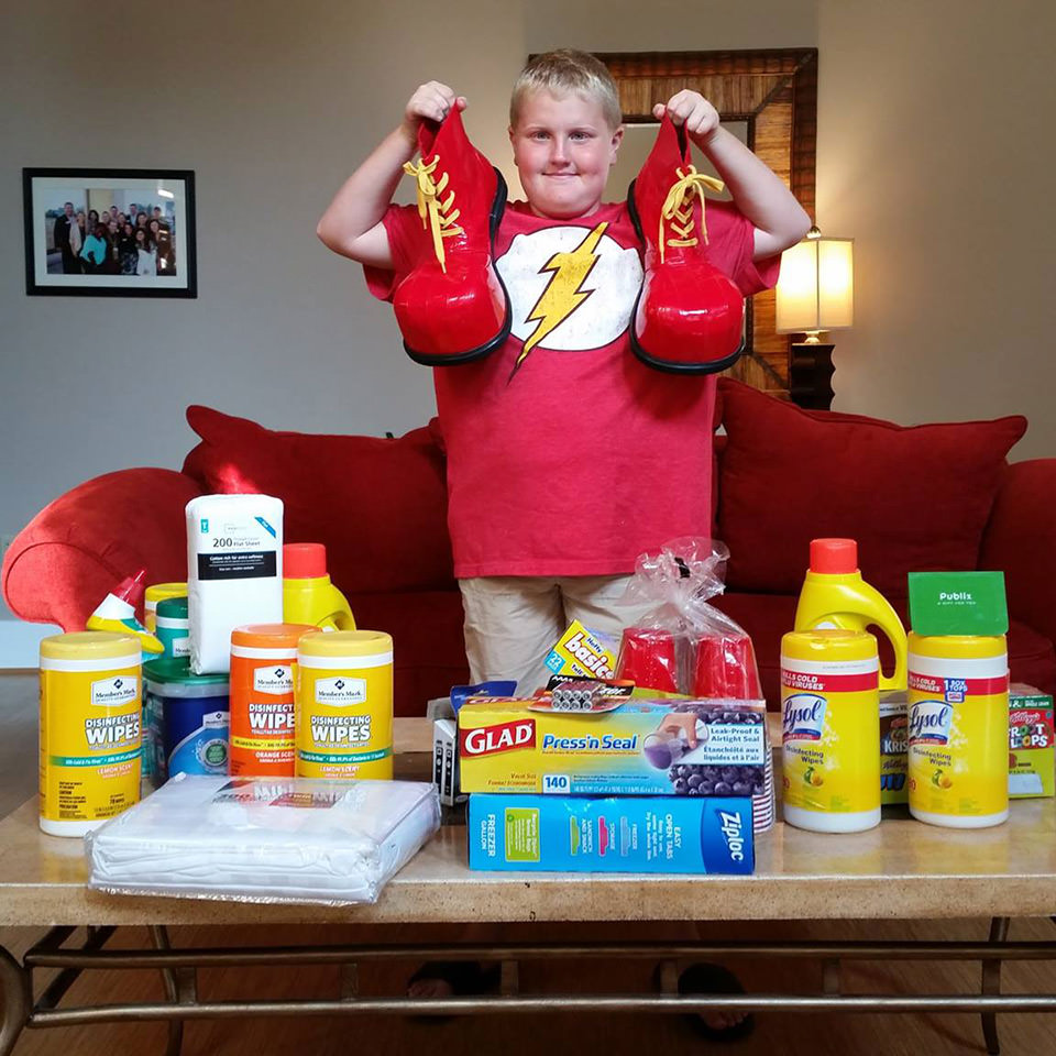 Young boy with supplies holding up ronald mcdonald shoes